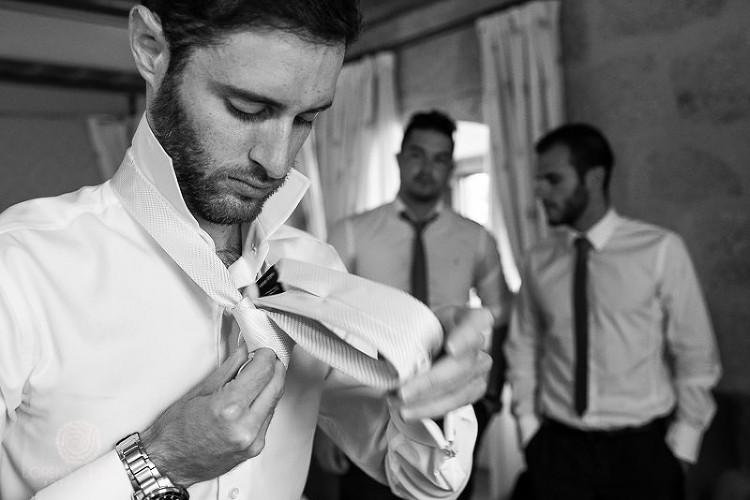 Novio haciendo nudo de la corbata en habitacion con los amigos - Fotografía de boda