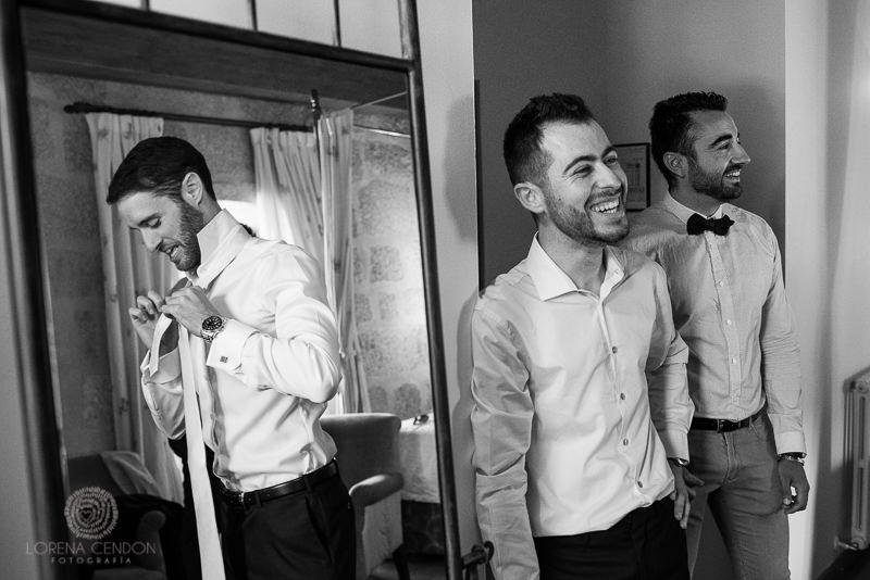 Novio con amigos en el momento de vestirse - Fotografía de boda