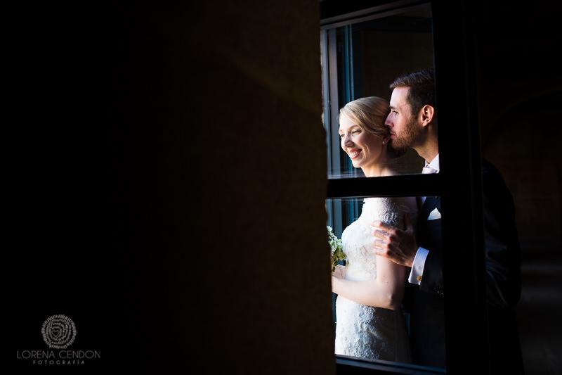 Novios mirando por una ventana - Fotografía de boda