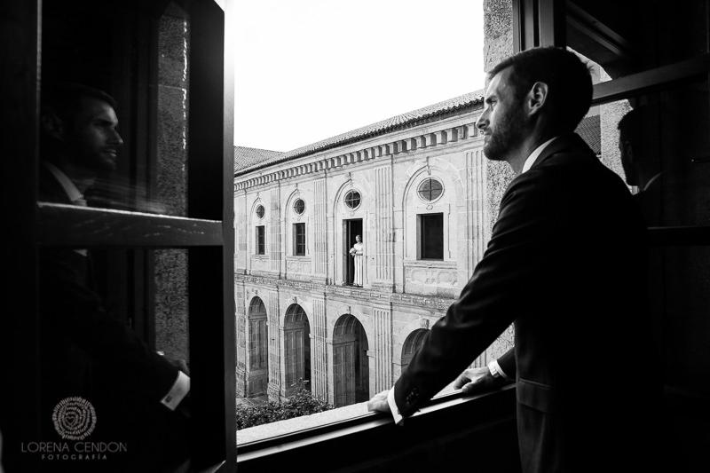 Novio mirando por la ventana con novia de fondo - Fotografía de boda