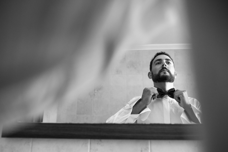 Novio en espejo con pajarita - Fotografía de boda