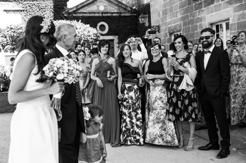 Novia llegando a la ceremonia con invitados - Fotografía de boda