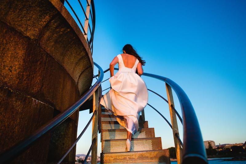 Novia de espaldas subiendo por la escalera - Fotografía de boda