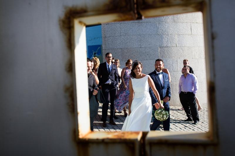 Novia , novio e invitados a través de una puerta llegando al aperitivo - Fotografía de boda