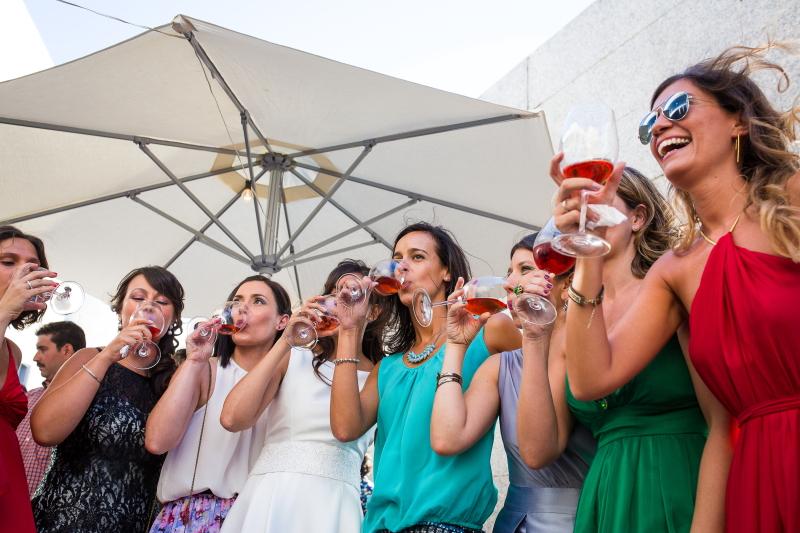 Invitadas con copa de vino en aperitivo - Fotografía de boda