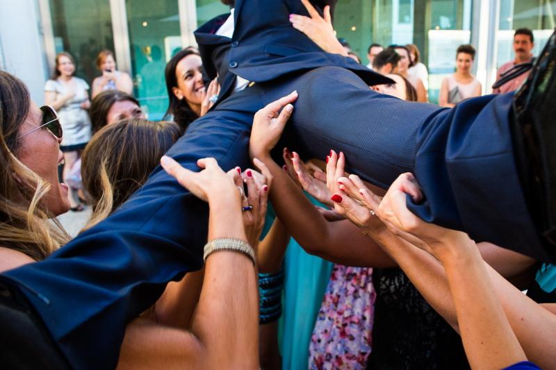 Invitadas levantando al novio - Fotografía de boda
