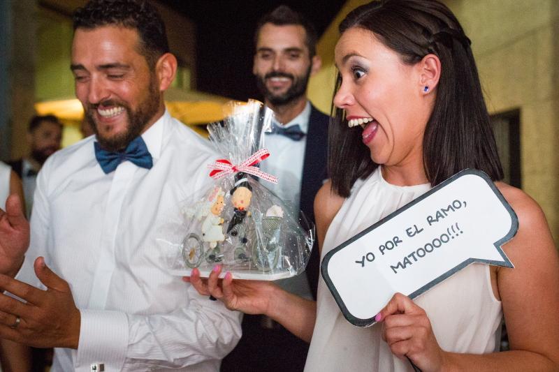 Invitada con la figura de los novios de la tarta - Fotografía de boda