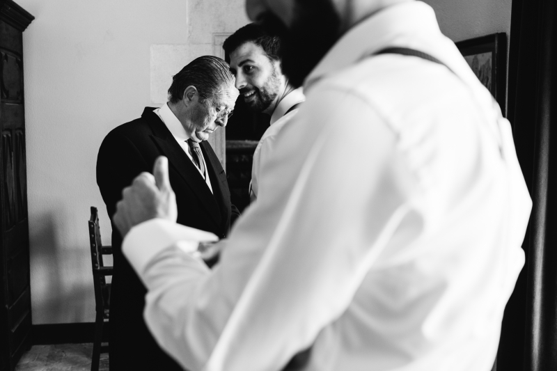 Padre ayudando a vestirse el novio en el Castillo de Tamarit - Fotografía de boda