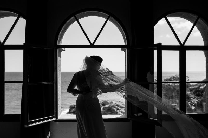 Novia con velo volando delante de una ventana en el Castillo de Tamarit - Fotografía de boda