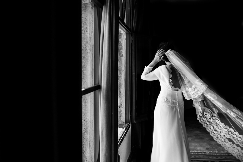 Novia de espaldas con velo volando - Fotografía de boda
