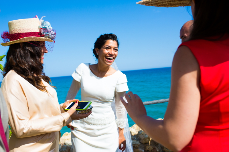 Novia con invitadas con tocados en el Castillo de Tamarit - Fotografía de boda