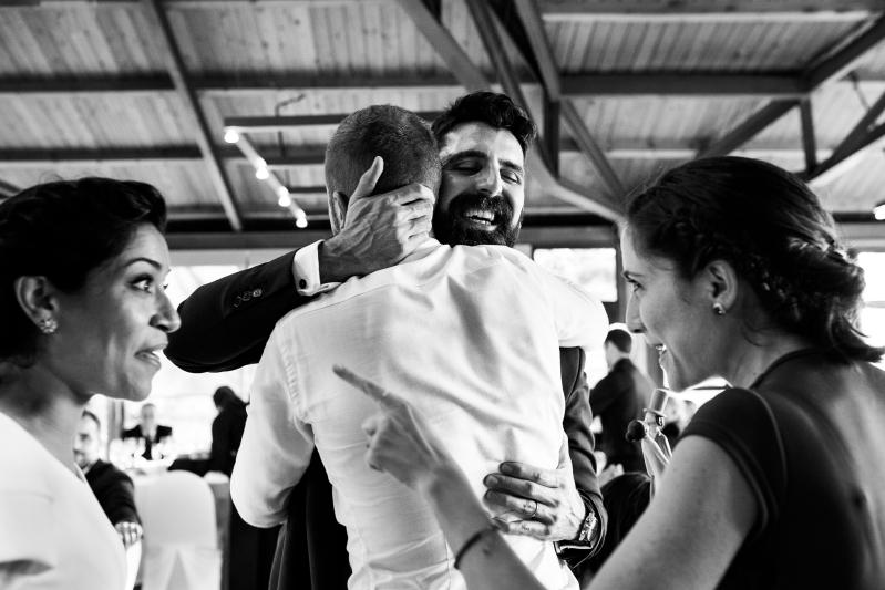 Novio abrazando a invitado cuando entrega los novios de la tarta - Fotografía de boda