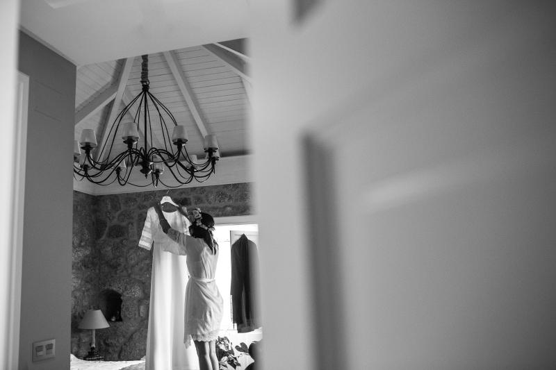 Fotografia de boda novia bajando su vestido de novia en la habitación