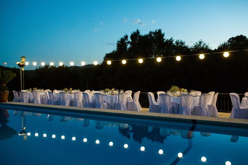 Mesas decoradas de boda alrededor de la piscina