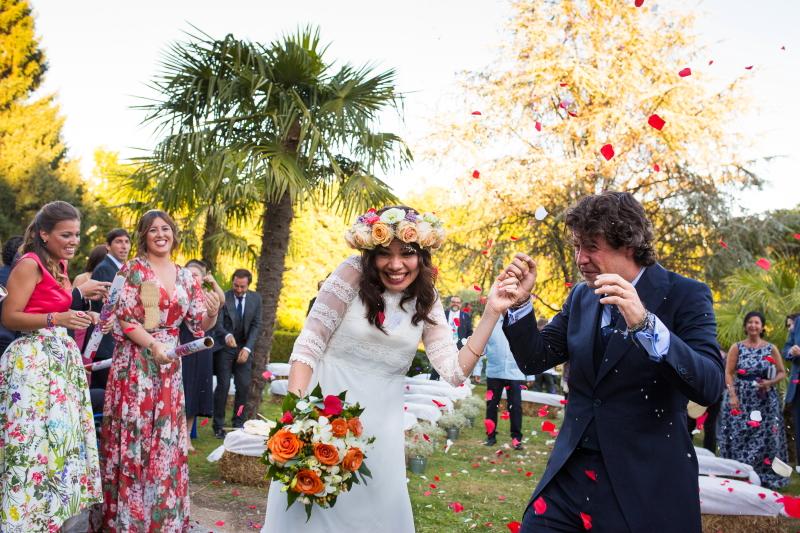 Novios con pétalos a la salida de la ceremonia en el día de su boda