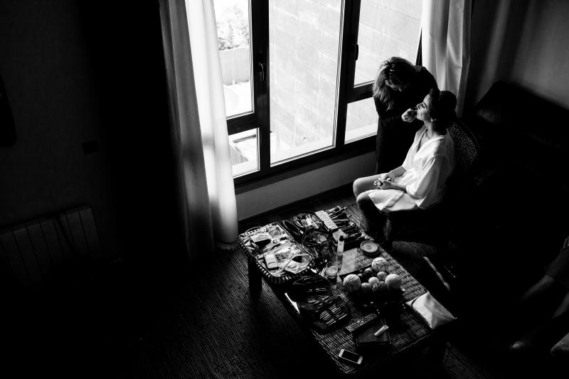 Novia con maquiladora cerca de una ventana el dia de su boda