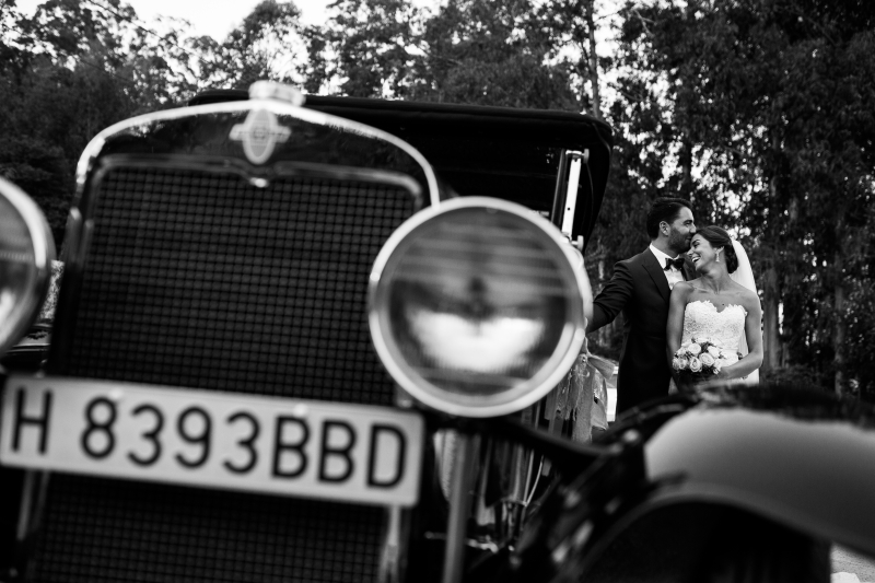 Novios posando con coche antiguo en su boda