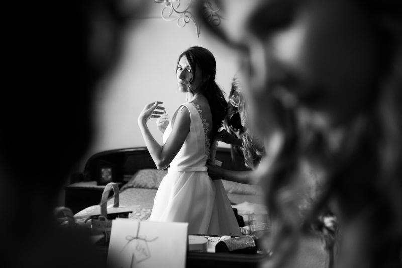 Novia el dia de su boda mientras se viste en la habitación con una amiga