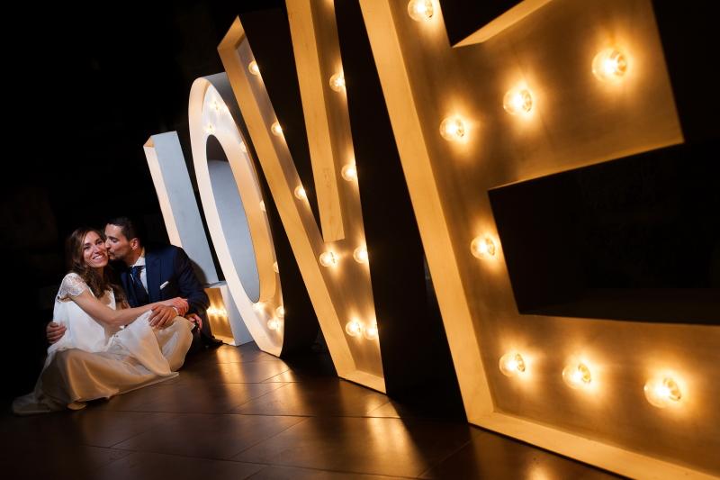 Pareja de novios el día de su boda posando con letras luminosas