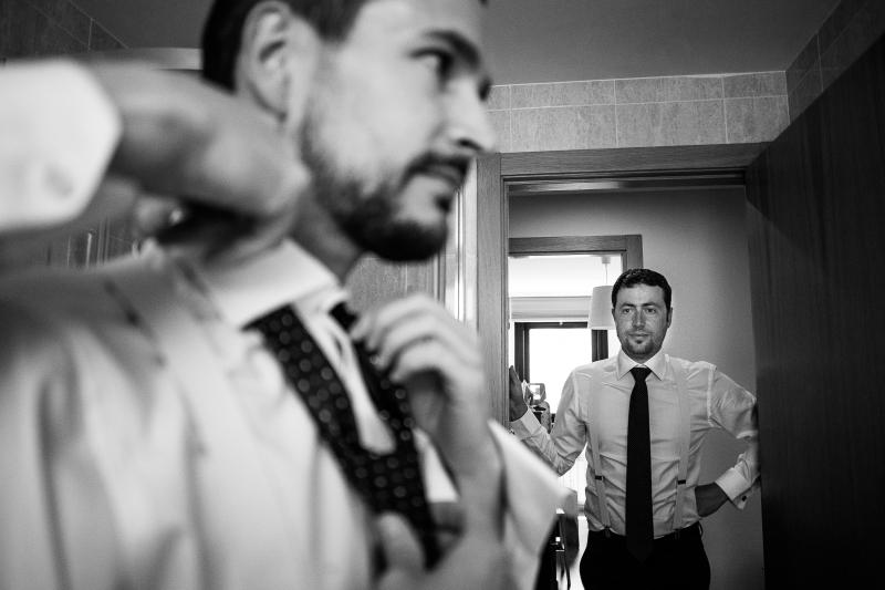 Novio mientras se pone la corbata el dia de su boda