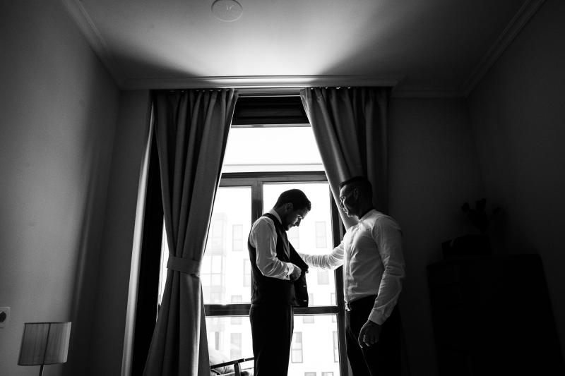 Novio delante de una ventana mientras se viste para su boda