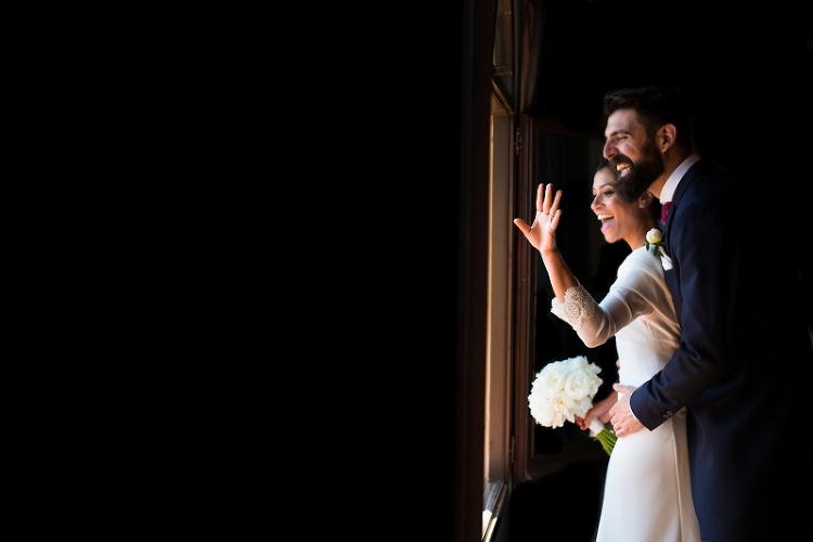 Novios saludando a traves de una ventana en el Castillo de Tamarit- Fotografía de boda