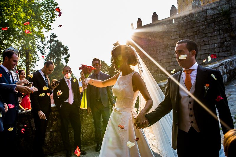 Historia de una boda en Castillo de Soutomaior mientras asomaba un rayito de sol en la salida de los novios Estibaliz y Fran a la salida de la ceremonia donde los invitados los recibían con miles de pétalos