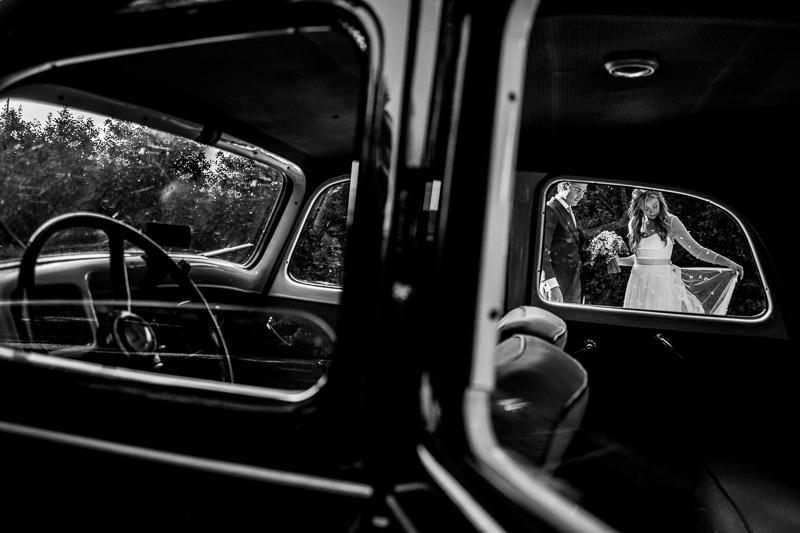 Fotografia de boda sesión de pareja de novios a traves del coche de boda en el Pazo el Castriño