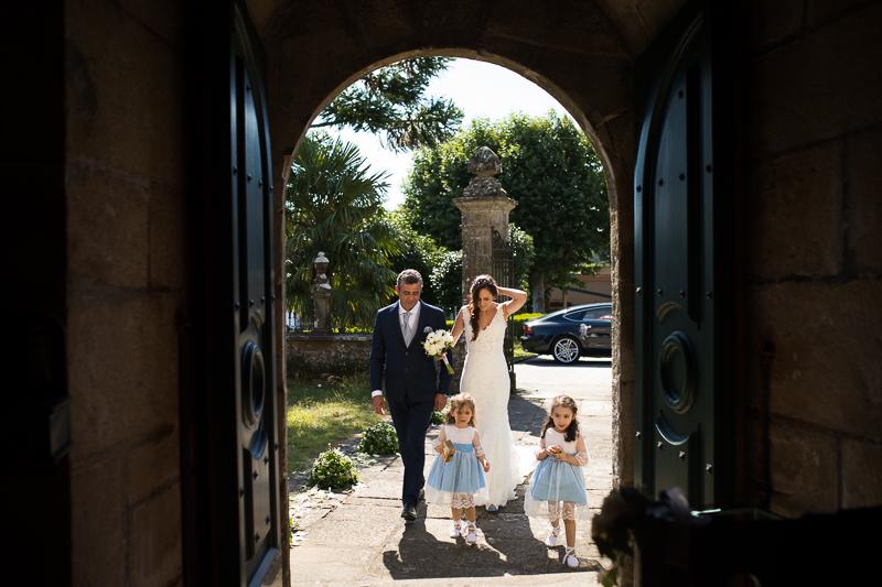 Fotografía de Boda Pazo Torre de Xunqueiras llegada de la novia con el padrino y las niñas de arras a la iglesia .