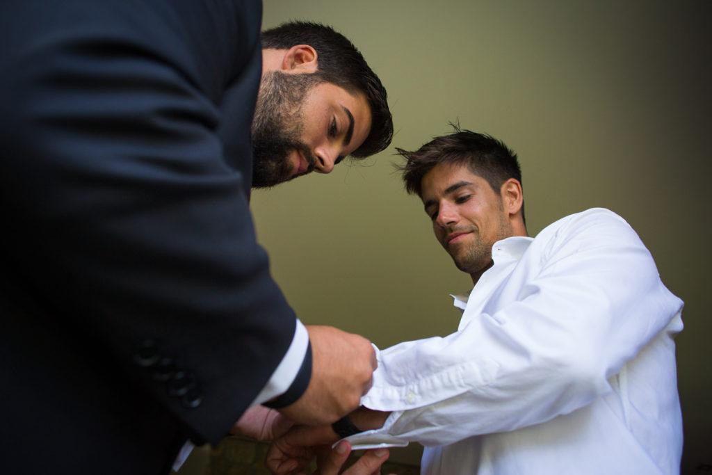 Fotografia de boda novio con su hermano mientras se viste colocando los gemelos