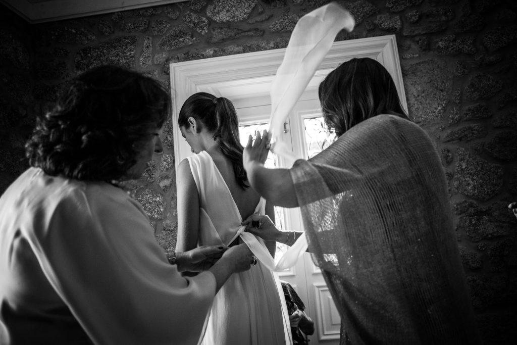 Fotografía de boda novia mientras se viste con su madre y una amiga