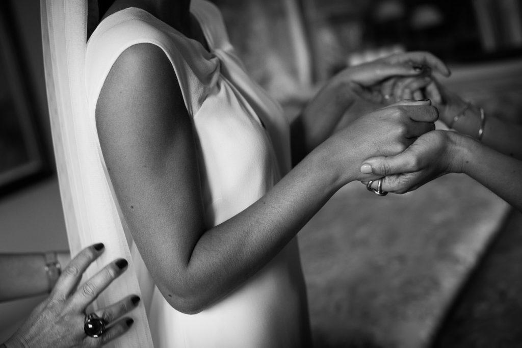 Fotografía de boda novia con su madre mientras se aprietan las manos