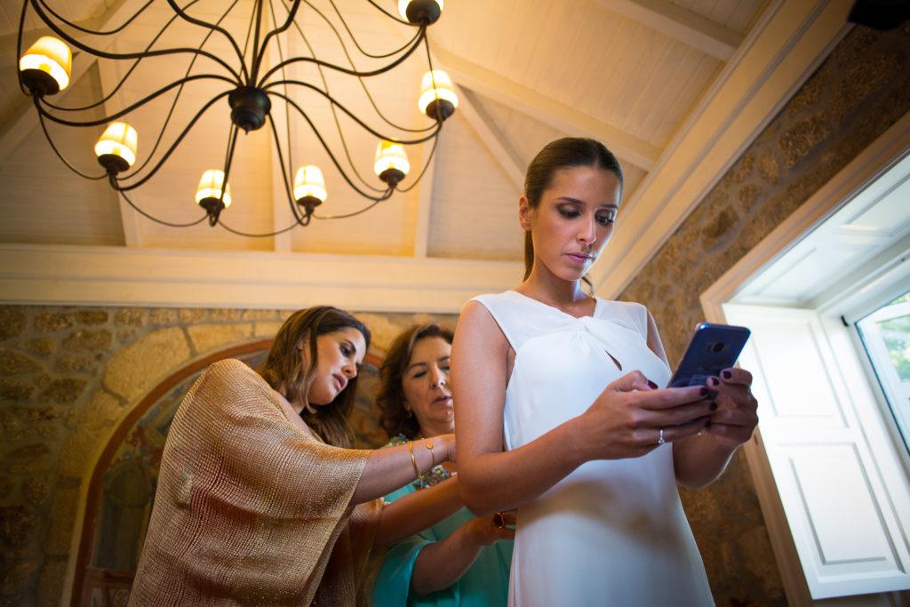 Fotografía de boda novia cuando se viste con su madre y una amiga