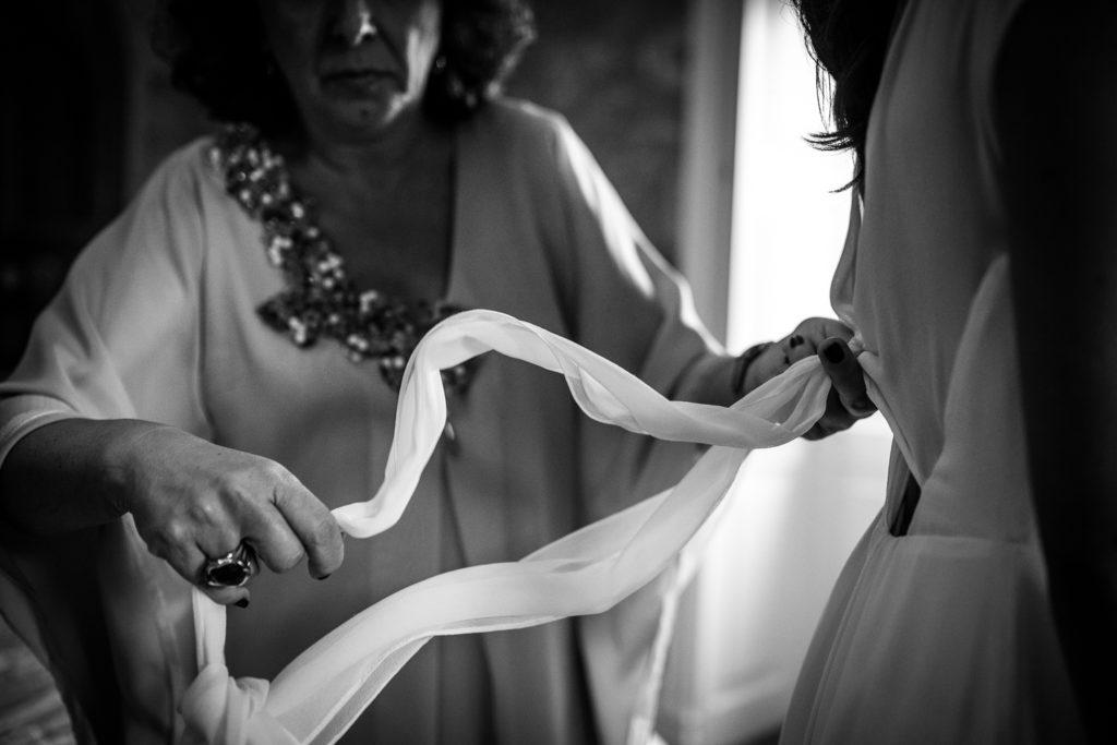 Fotografía de boda madre colocando el lazo del vestido