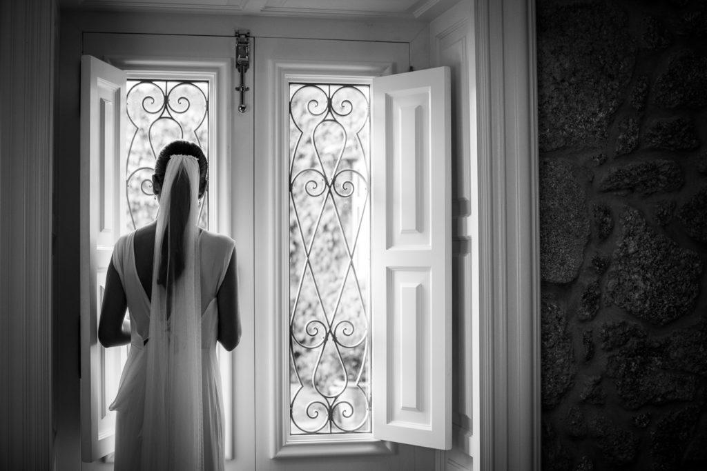 Fotografía de boda novia viendo por la ventana