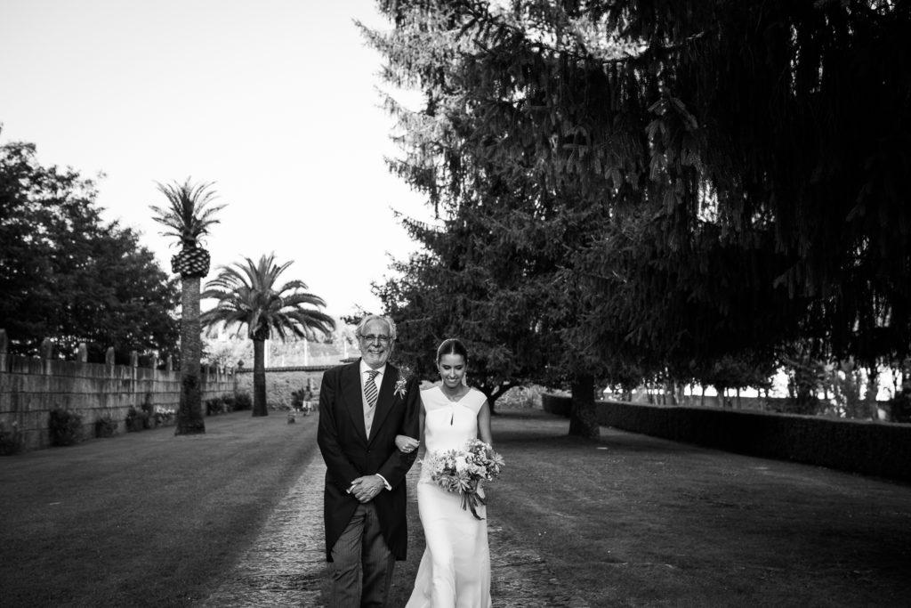 Fotografía de boda novia con su padre cuando entra en la ceremonia