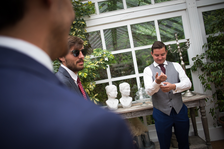 Fotografia de bodas novio mientras se viste con hermanos