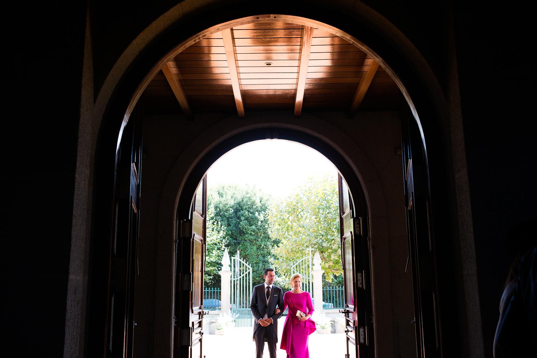 Fotografía de boda novio con madrina en la entrada de la iglesia