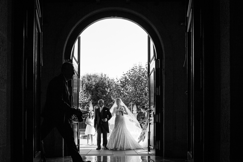 Fotografía de boda novia con padrino en la entrada de la iglesia