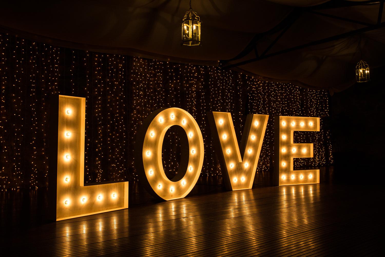 Fotografía de boda letras grandes con luces que pone LOVE