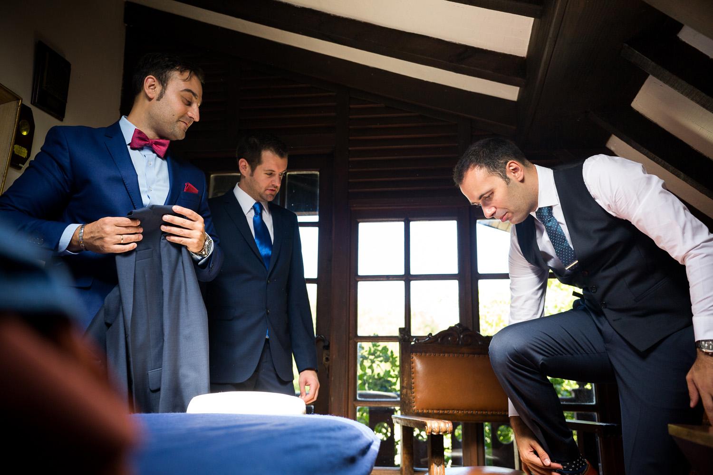 Fotografia de boda novio con los invitados mientras se viste