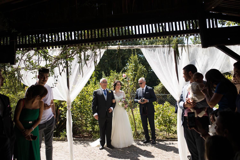 Fotografia de boda novia con el padrino entrando en la ceremonia