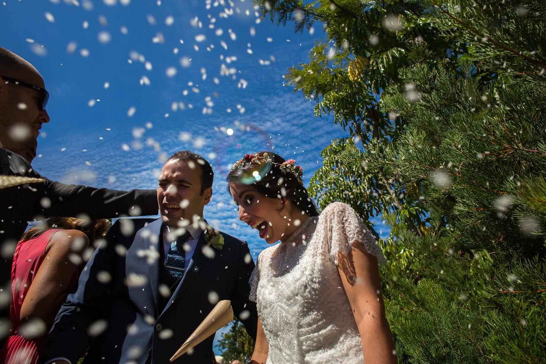 Fotografia de boda pareja de novios en la salida de la ceremonia con pétalos