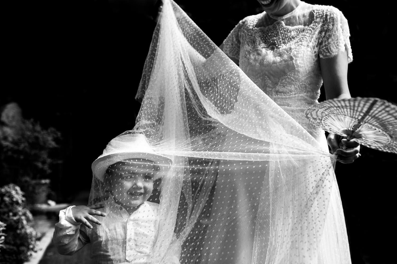 Fotografia de boda niño jugando con el velo de la novia
