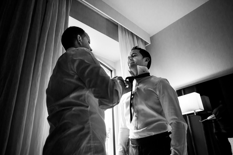 Fotografia de boda novio en los preparativos con su hermano mientras le pone la corbata