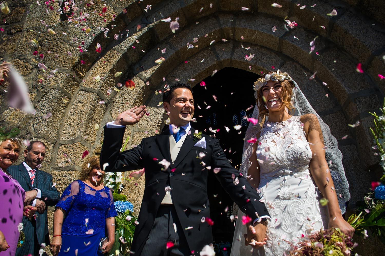 Fotografia de boda pareja de novios en la salida de iglesia con pétalos